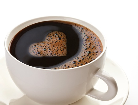 Coffee cup and saucer on a white background. Foam in the form of the heart. photo