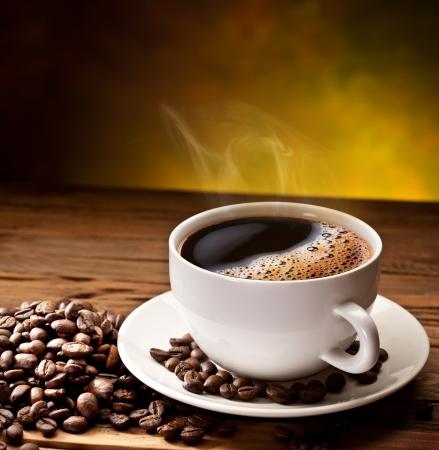 Taza de café y platillo en una mesa de madera. Fondo oscuro.