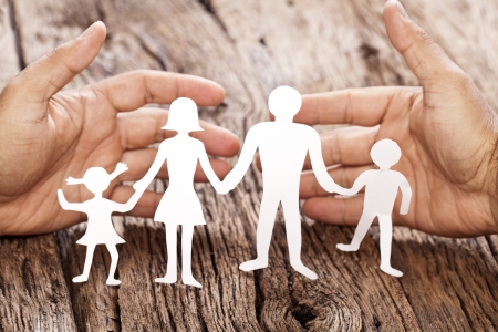 gently: Cardboard figures of the family on a wooden table. The symbol of unity and happiness. Hands gently hug the family.