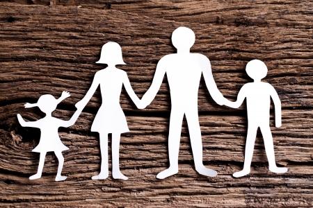 familia unida: Figuras de cart�n de la familia en una mesa de madera. El s�mbolo de la unidad y la felicidad. Foto de archivo
