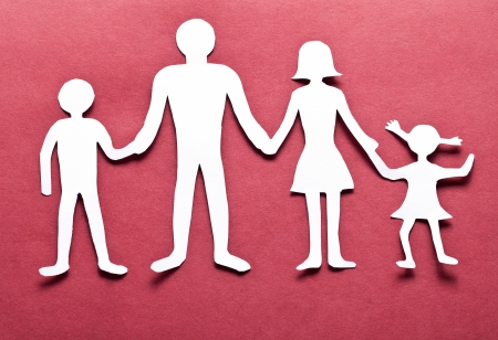 Cardboard figures of the family on a red background. The symbol of unity and happiness. photo
