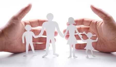 защита: Картонные фигуры семьи на белом фоне. Символом единства и счастья. Руки нежно обнять семьи. Фото со стока