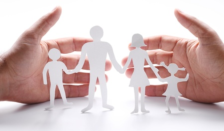 protect: Cardboard figures of the family on a white background. The symbol of unity and happiness. Hands gently hug the family. Stock Photo