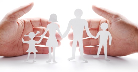 gently: Cardboard figures of the family on a white background. The symbol of unity and happiness. Hands gently hug the family. Stock Photo