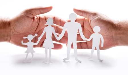protect family: Cardboard figures of the family on a white background. The symbol of unity and happiness. Hands gently hug the family. Stock Photo