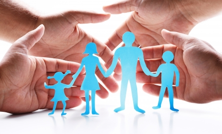 Cardboard figures of the family on a white background  The symbol of unity and happiness  Hands gently hug the family  photo