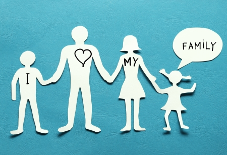 Cardboard figures of the family on a blue background  The symbol of unity and happiness  photo