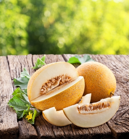 honeydew: Melon with slices and leaves on a old wooden table  Stock Photo