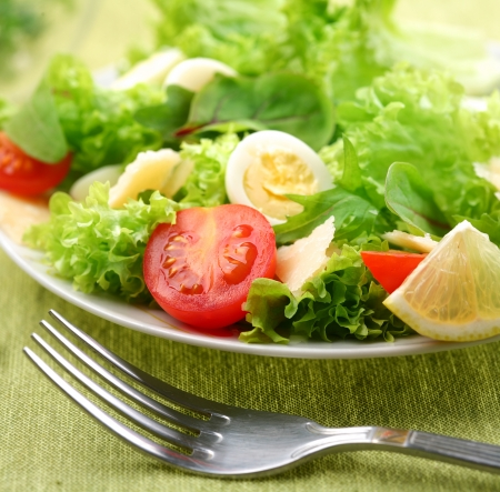 Fresh salad with tomato and quail eggs on a green tablecloth
