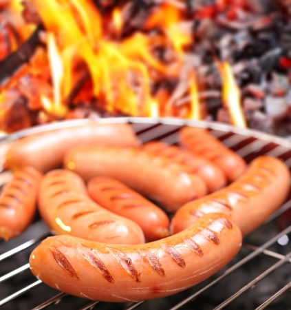 sizzle: Sausages on a grill  In the background in bonfire