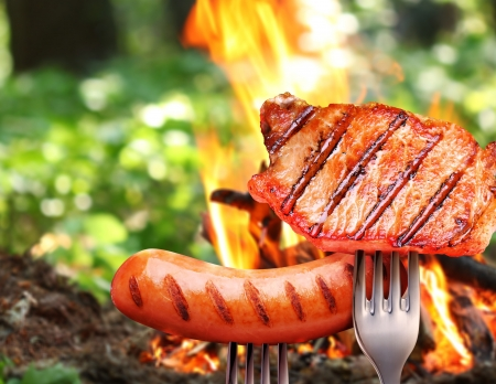 sizzle: Sausage and steak on a fork  In the background a bonfire in the forest
