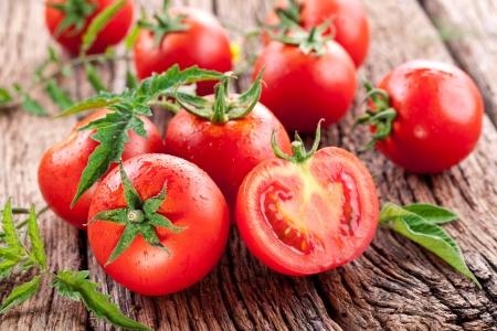 Tomatoes, cooked with herbs for the preservation on the old wooden table. Stockfoto