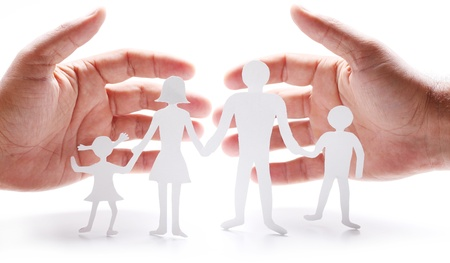 Cardboard figures of the family on a white background. The symbol of unity and happiness. Hands gently hug the family. photo