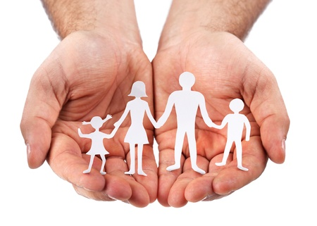 linked hands: Cardboard figures of the family on a white background. The symbol of unity and happiness. Hands gently hug the family. Stock Photo
