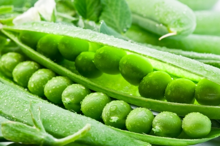 green peas: Pods of green peas on a background of leaves. Stock Photo