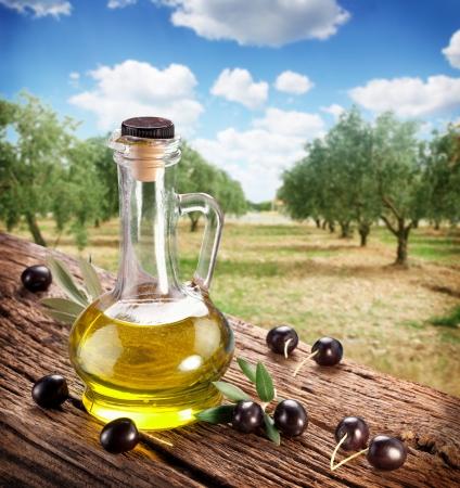 aceite de oliva: Aceitunas negras con la botella de aceite en una mesa de madera sobre un fondo de jardín de oliva