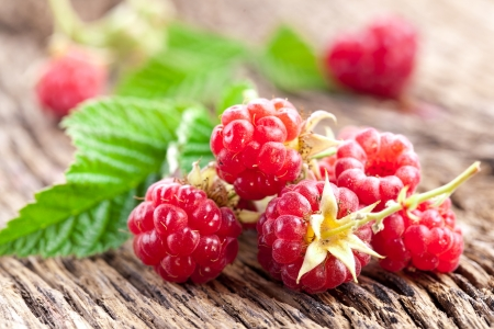 raspberries: Raspberries with leaves on the old wooden table