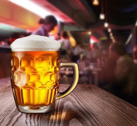 unbottled: Glass of light beer on a dark pub
