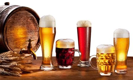 vasos de cerveza: Barril de cerveza con vasos de cerveza sobre una mesa de madera aislado en un fondo blanco Este archivo contiene trazado de recorte Foto de archivo