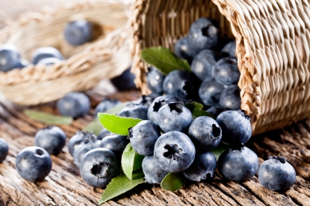 Blueberries have dropped from the basket on an old wooden table