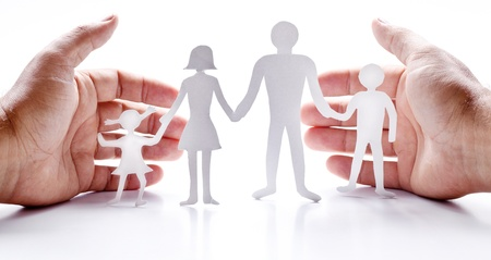 linked hands: Cardboard figures of the family on a white background  The symbol of unity and happiness  Hands gently hug the family