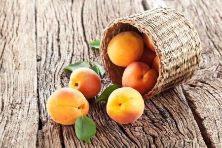 canasta de frutas: Albaricoques con hojas sobre la mesa de madera vieja