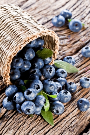 Blueberries have dropped from the basket on an old wooden table  photo