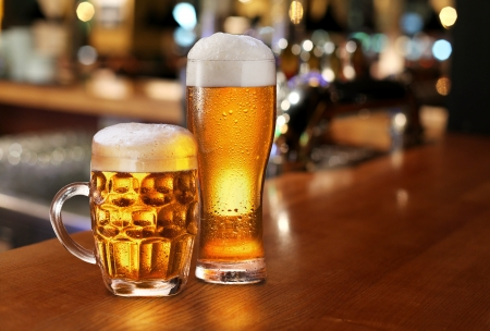 vasos de cerveza: Vidrio de cerveza ligera en un pub oscuro