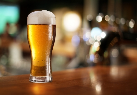 Glas licht bier op een donkere kroeg Stockfoto