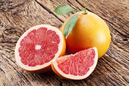 grapefruit: Grapefruit with slices on a wooden table. Stock Photo