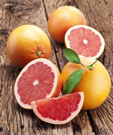 toronja: Pomelo con las rebanadas en una tabla de madera.