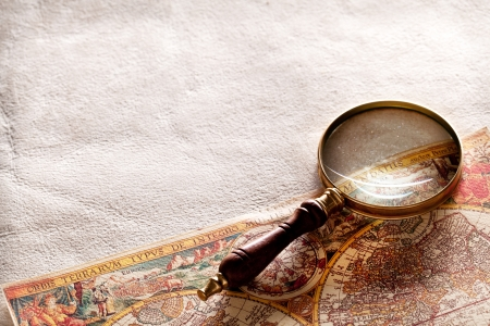 Magnifying glass on old parchment. Stock Photo - 16873174