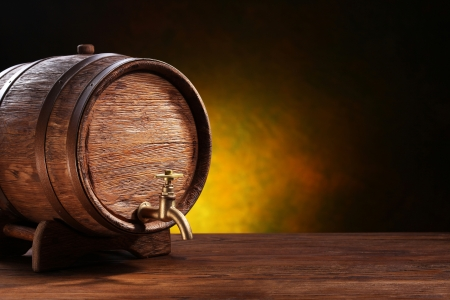 Old oak barrel on a wooden table  Behind blurred dark background  Stock Photo