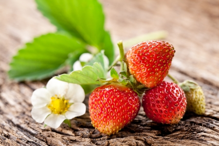 honeyed: Strawberries with leaves on the old wooden table