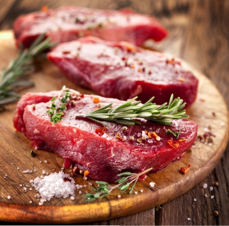 raw beef: Raw beef steak on a dark wooden table.