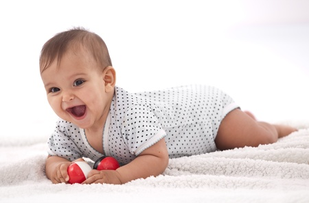 hispanic baby: Laughing baby girl with small balls laying on the floor