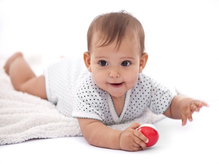 head toy: Little baby girl with small ball laying on the floor