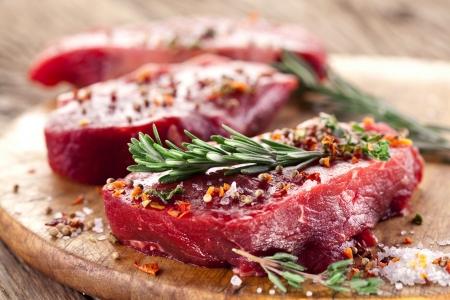 carnes rojas: Filete de carne cruda en una mesa de madera oscura