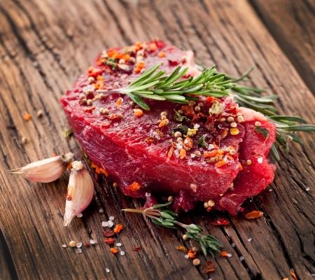 Rohes Rindfleisch Steak auf einem dunklen Holztisch