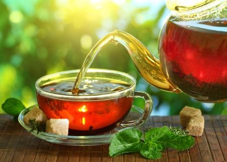 kettles: Verter el t� de una tetera en una taza sobre un fondo borroso de la naturaleza