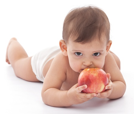 nibble: Baby girl attacking an apple  Isolated on a white background