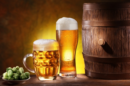 Beer glasses with a wooden barrel  Background - dark yellow gradient  Stock Photo - 18165720