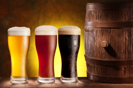 Three beer glasses with a wooden barrel  Background - dark yellow gradient  Stock Photo - 18165728