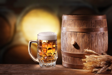 Beer glasses with a wooden barrel  Background - dark yellow gradient  Stock Photo - 18165737