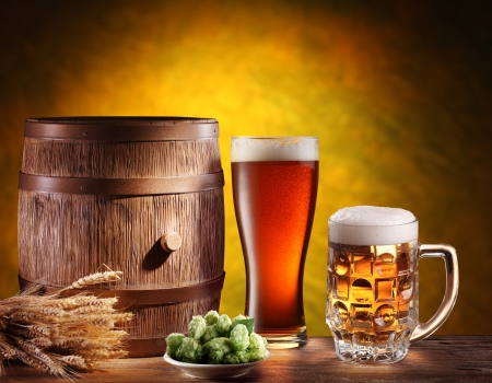 Beer glasses with a wooden barrel  Background - dark yellow gradient  Stock Photo - 18165751
