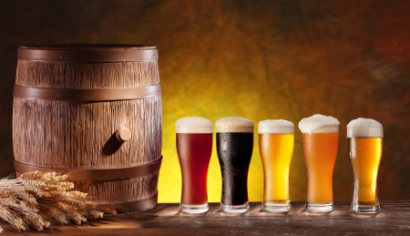 Assortment of beer glasses with a wooden barrel Background - dark yellow gradient