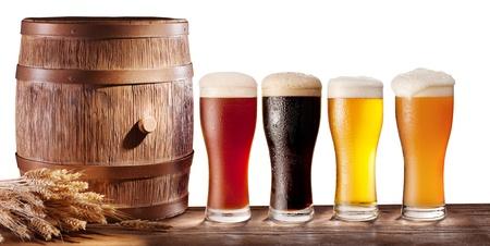cerveza: Surtido de vasos de cerveza con un barril de madera sobre un fondo blanco