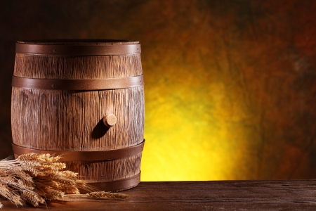 cask: Wooden barrel with wheat on a dark yellow background  Stock Photo
