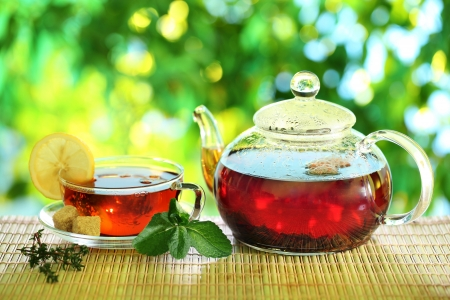 Cup of tea and teapot on a blurred background of nature  photo