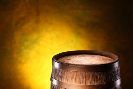 Wooden barrel on a dark yellow background. photo